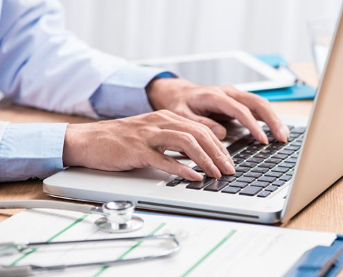 GP typing notes on a laptop