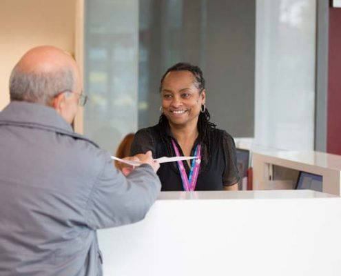 Man receiving forms from receptionist